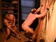 Suspended on St. Andrews Cross I paddle this big bodybuilder musc