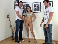 Two guys helping teen girl during an erotic photosession
