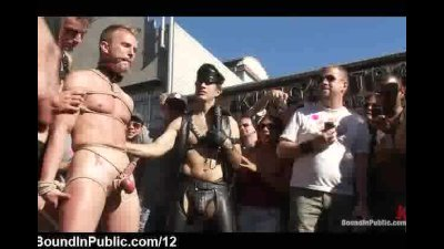 Bound gays with linked balls in bdsm fair in the streets