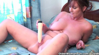 Classy granny plays with her dildo collection